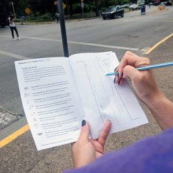 Person using ChalkTalk booklet to observe city streets.